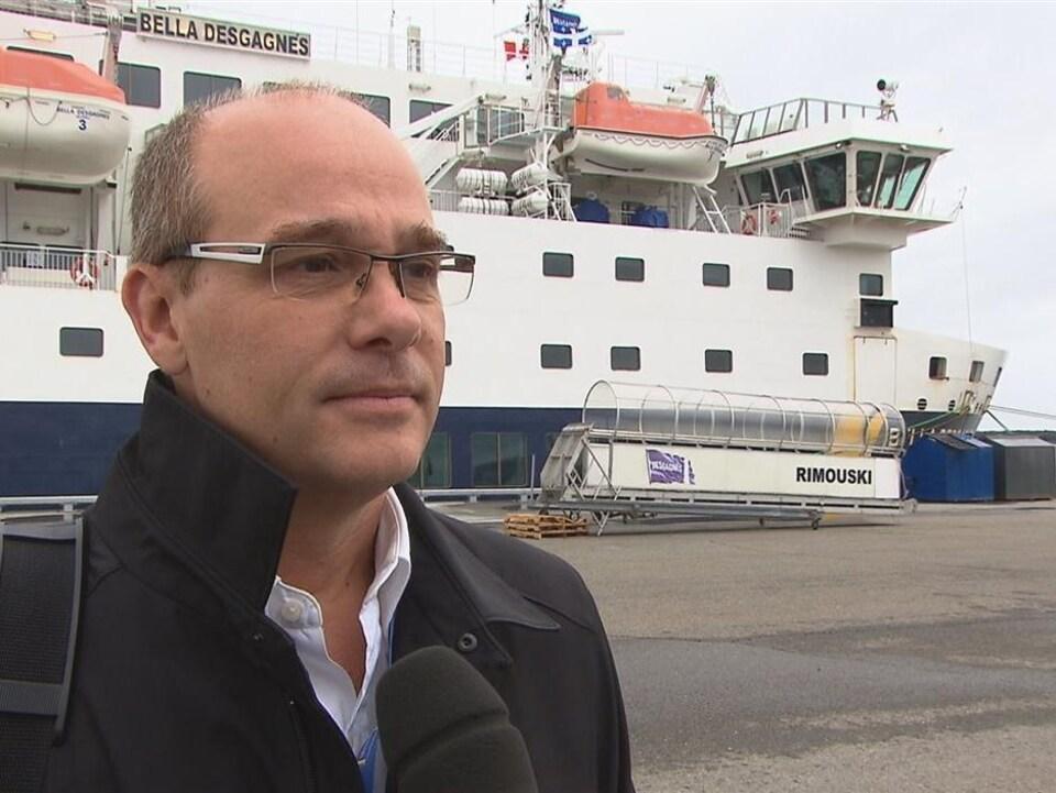 Francis Roy devant un bateau.