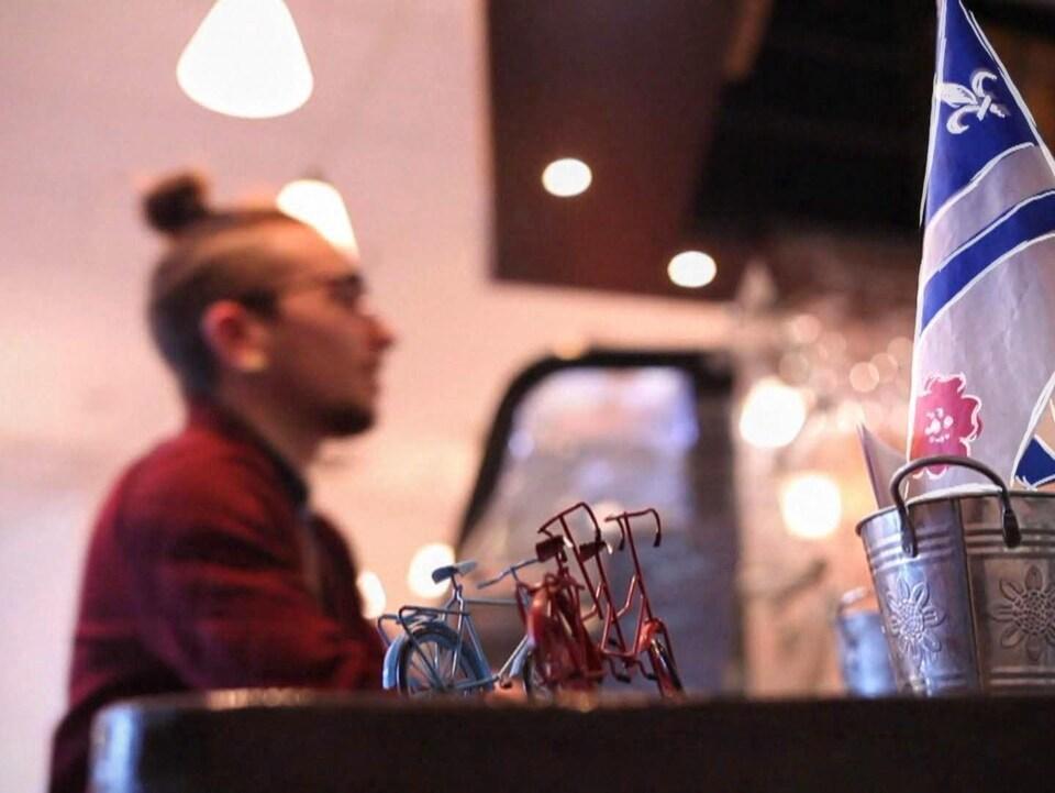 Em Lamache commande une boisson dans un café francophone d'Edmonton. En premier plan, on peut voir un drapeau représentant la francophonie albertaine.