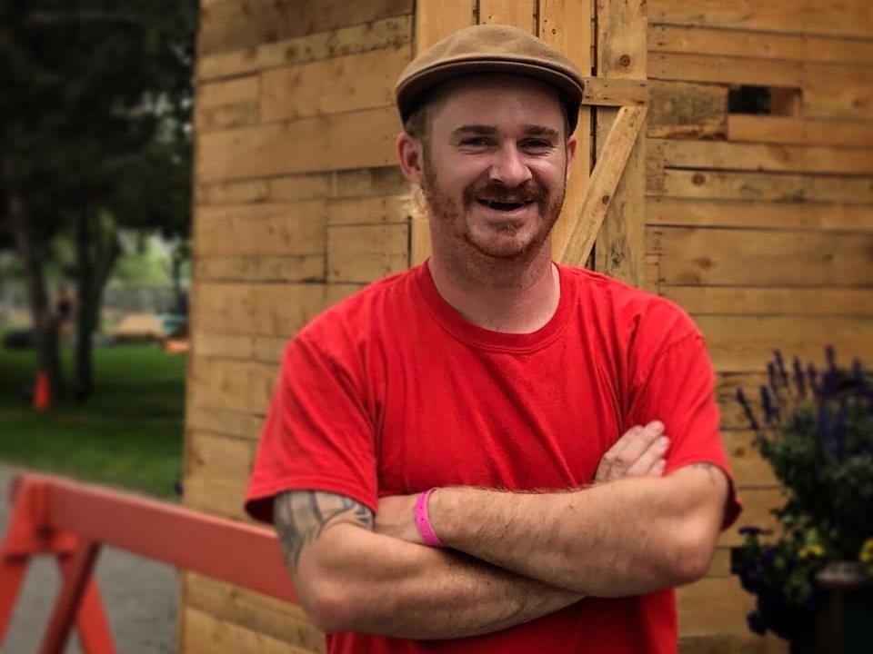 Un homme portant une casquette pose les bras croisés, souriant.