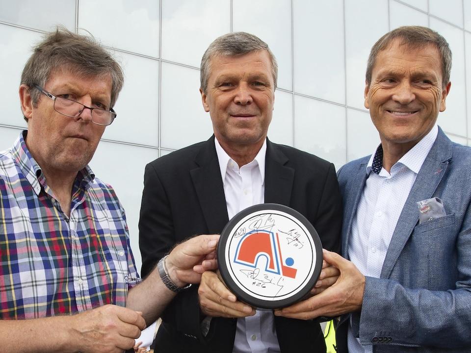 Les trois frères tiennent une rondelle de hockey géante avec leurs signatures, sur laquelle est imprimé un logo des Nordiques.