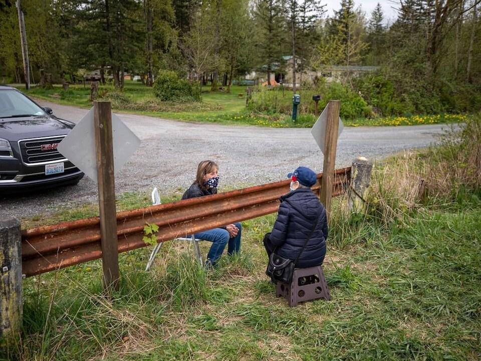 Due donne Assis su ciascun lato di A Recinzione presso il confine del Canada-American discutere.'une clôture à la frontière canado-américaine discutent.