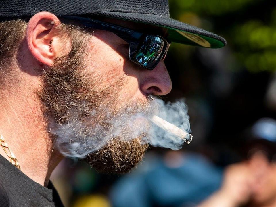 Un homme barbu fume un joint.