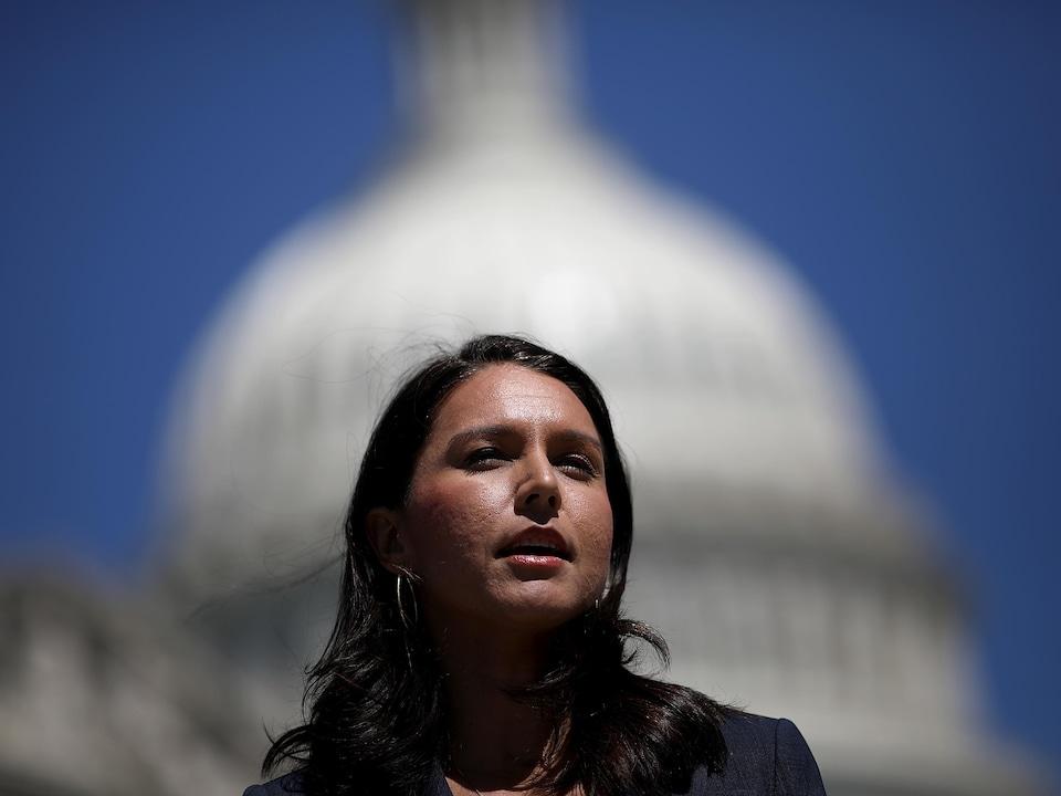Une femme regarde à l'horizon devant la coupole du Capitole à Washington.
