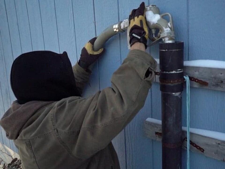 Un livreur d'eau potable remplit une citerne dans une maison de Garden Hill.