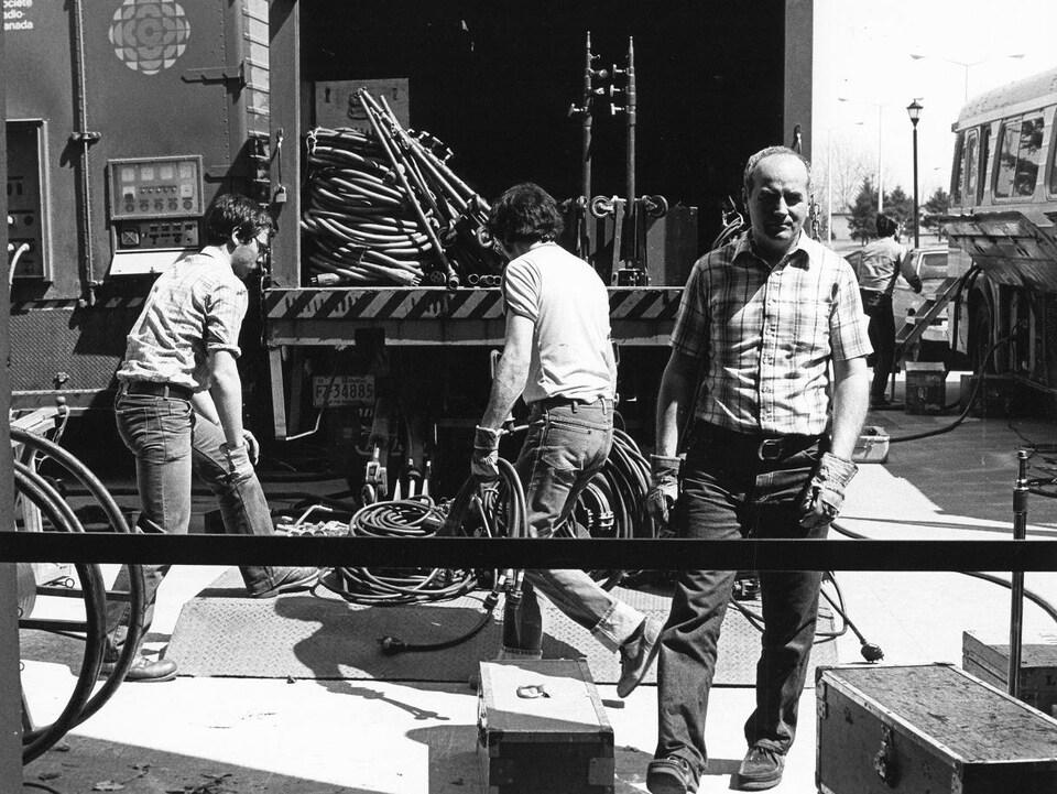 Des techniciens s'affairent près d'un camion d'équipement de Radio-Canada.
