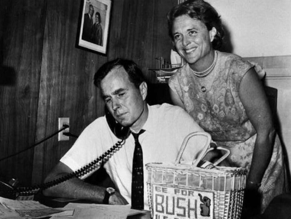 George Bush effectue des appels pour sa campagne électorale et Barbara Bush pose derrière lui.