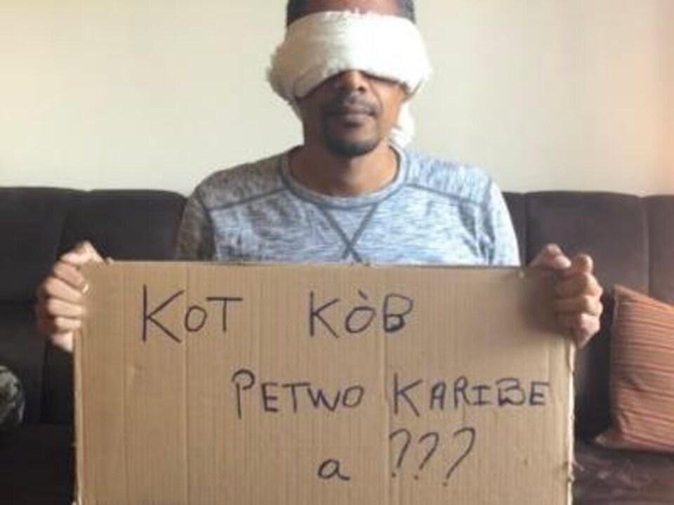 Un homme qui a les yeux bandés tient une pancarte en carton.