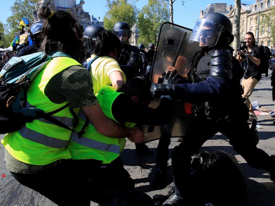 Des gilets jaunes se font repousser par un policier casqué qui porte un bouclier.