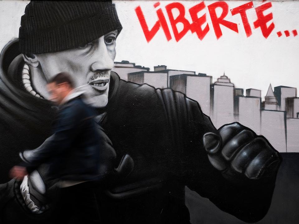 Un homme passe rapidement devant une murale représentant l'ancien boxeur français Christophe Dettinger dans une rue de Paris.
