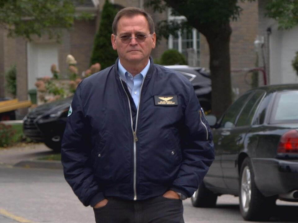 M. Primeau marche dans la rue, les mains dans les poches, vers la caméra.
