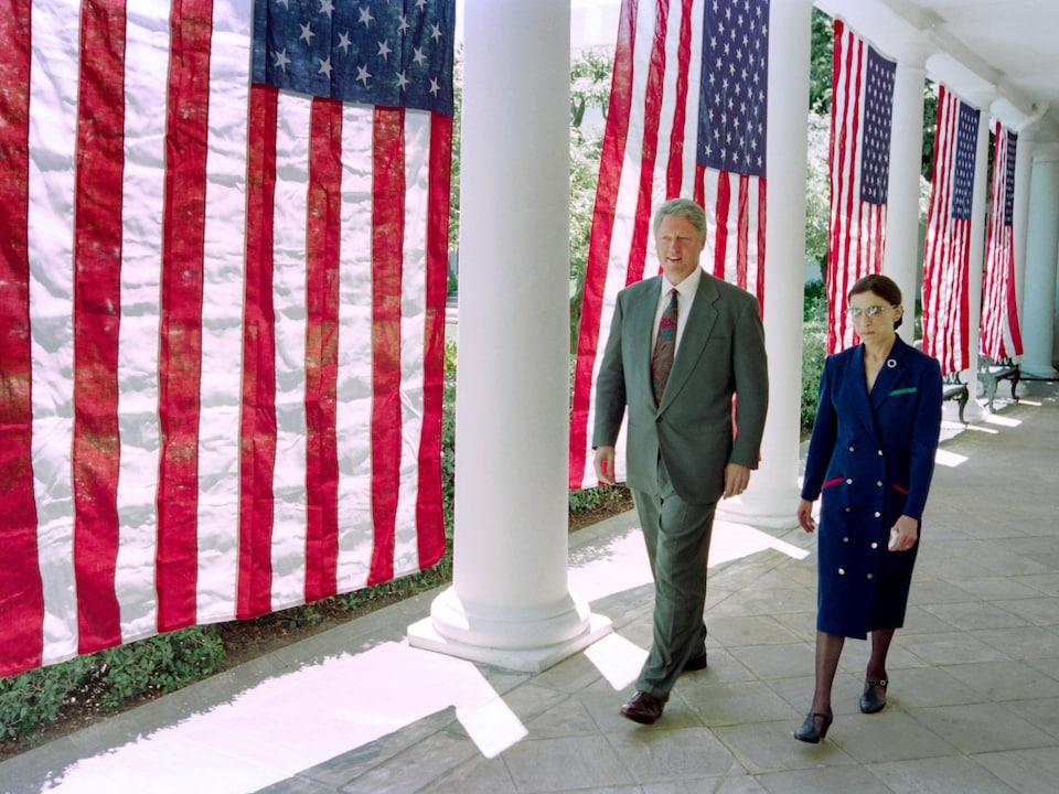 Bill Clinton et Ruth Bader Ginsburg marchent côte à côte devant des drapeaux américains.