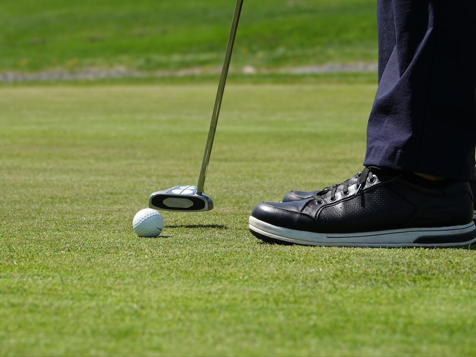 Plan rapproché d'un bâton de golf tenu par un joueur s'apprêtant à frapper la balle.