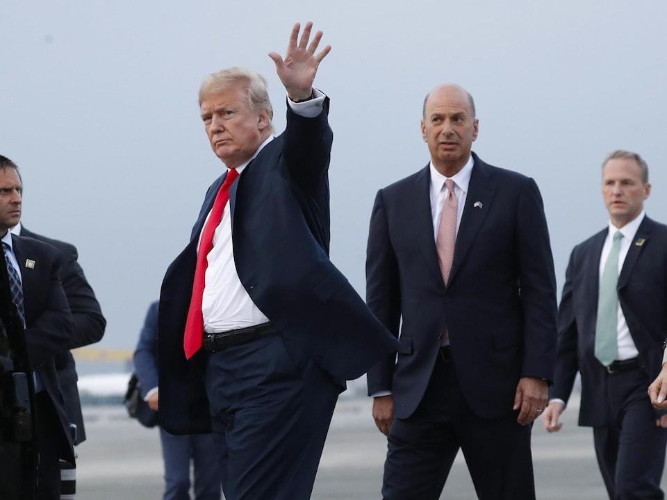 Donald Trump salue en levant la main, aux côtés de Gordon Sondland.