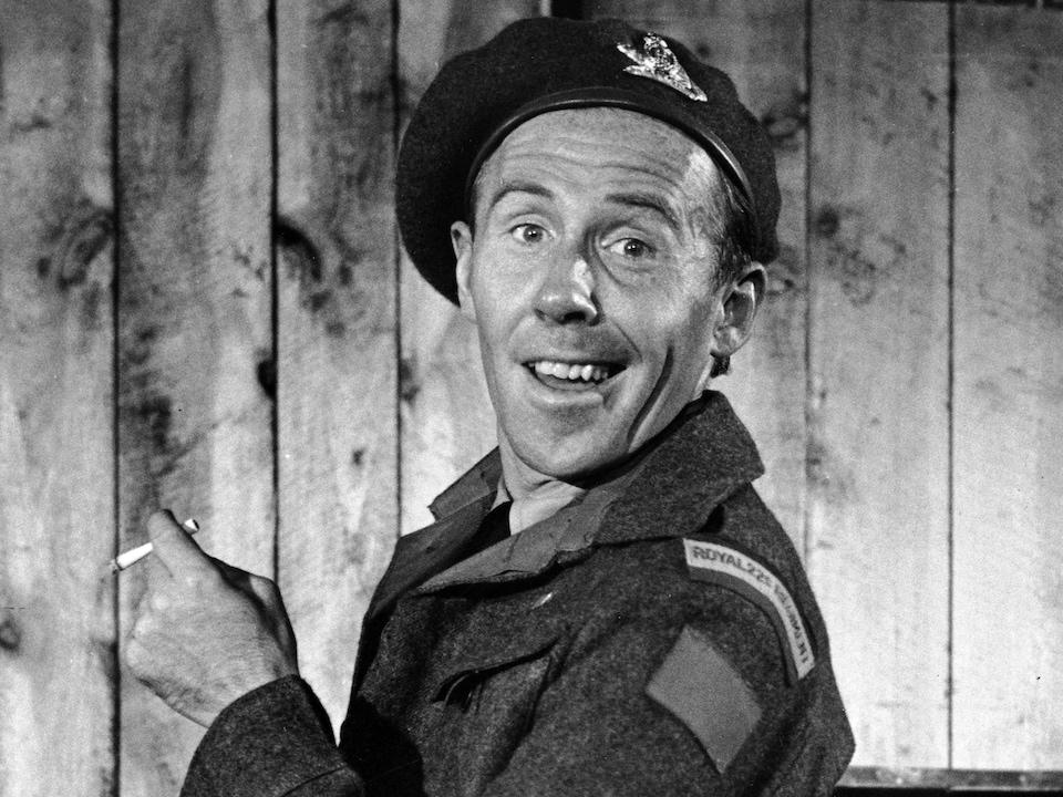 Dans son uniforme de soldat du Royal 22e Régiment, Tit-Coq (Gratien Gélinas) est tout gaillard, une cigarette à la main.