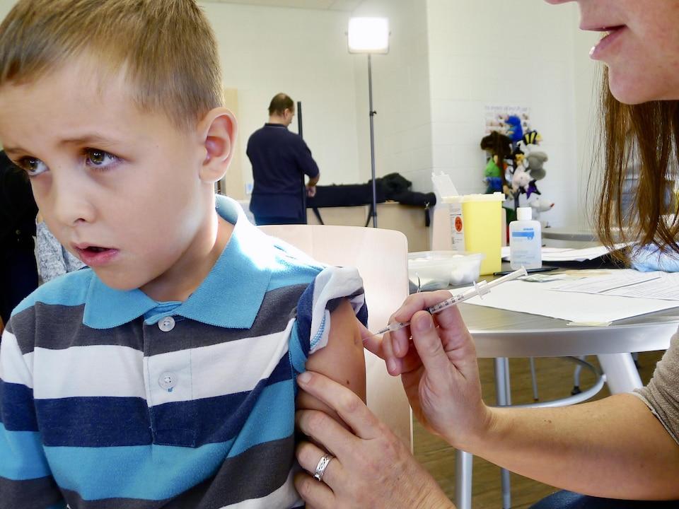 Un garçon se fait faire une piqûre au bras.