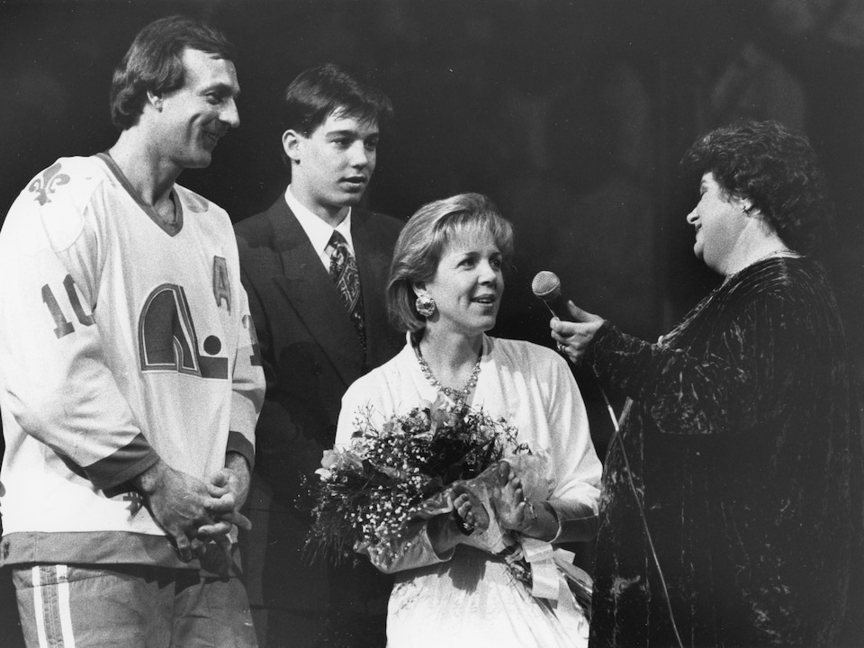Guy Lafleur honoré lors de son dernier match avec les Nordiques au Colisée, en 1991, avec son fils Martin, sa femme, Lise Lafleur, et la chanteuse Ginette Reno. Ginette Reno tient son micro et Lise tient un bouquet de fleurs.