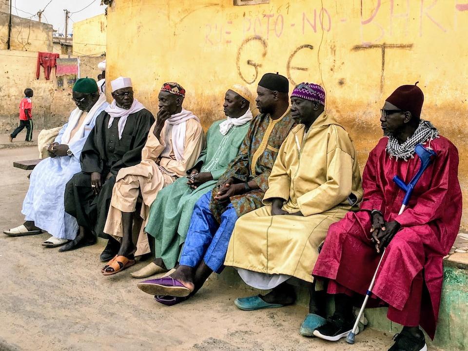 Plusieurs hommes aux vêtements colorés assis sur un banc.