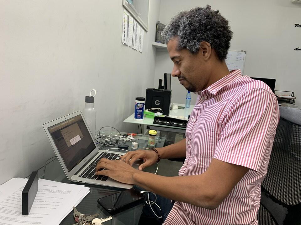 Un homme, assis, de profil, pianote sur son ordinateur portable.