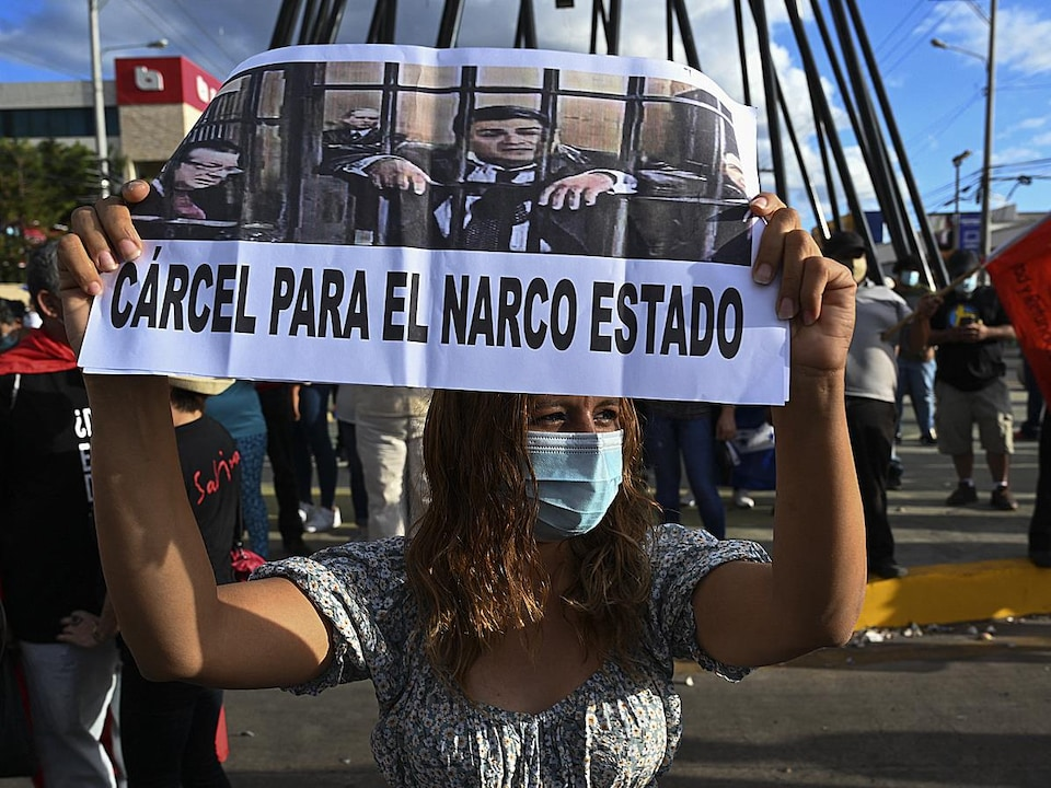 Entourée d'autres manifestants, une femme tient une pancarte qui montre le président du Honduras, Juan Orlando Hernandez, en prison.