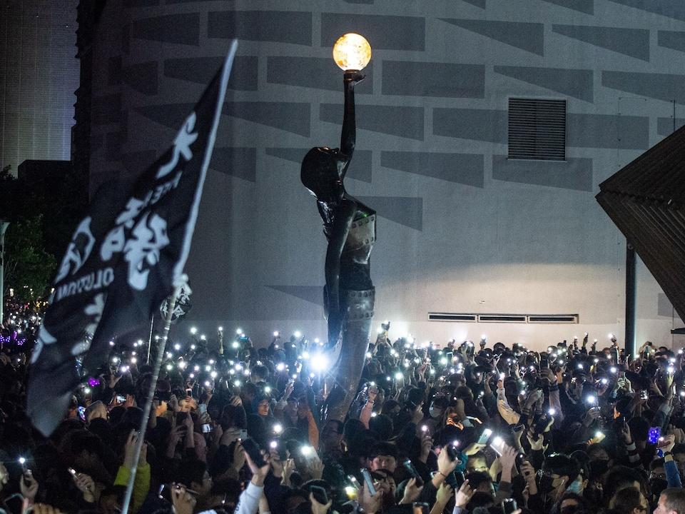 Des centaines de personnes brandissent les torches de leur cellulaire.