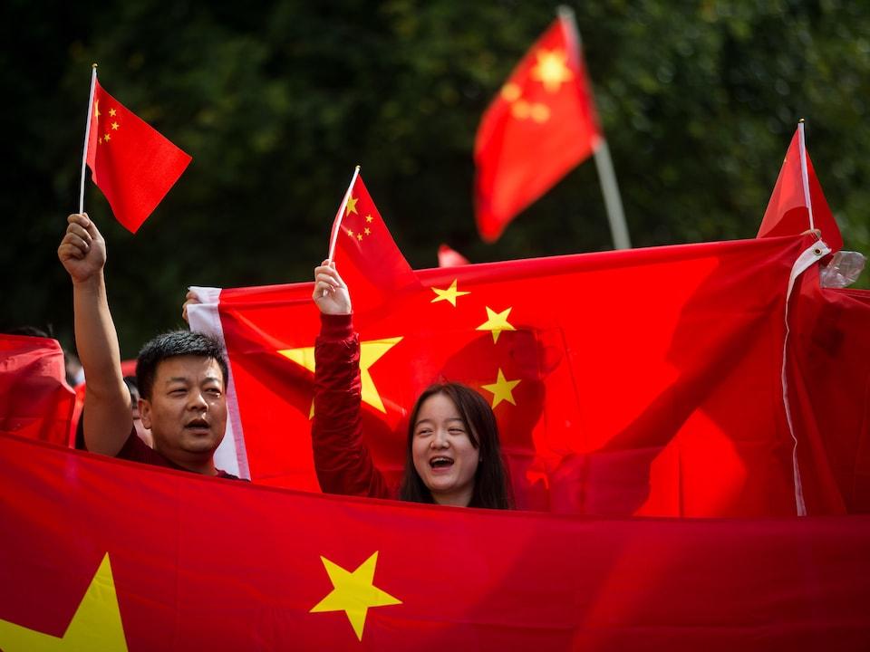 Des manifestants brandissent des drapeaux chinois.