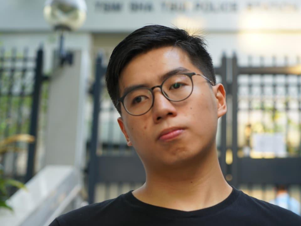 Ernie devant un immeuble clôturé à Hong Kong.