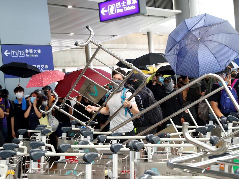 Des manifestants ont mis en place des barricades à l'extérieur des terminaux à l'aéroport international de Hong Kong.