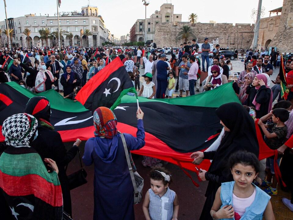 Des femmes, des hommes et des enfants portant des drapeaux dans une place publique.