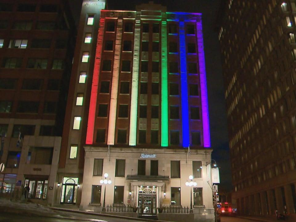 La façade de l'hôtel Marriott est illuminée aux couleurs de l'arc-en-ciel.