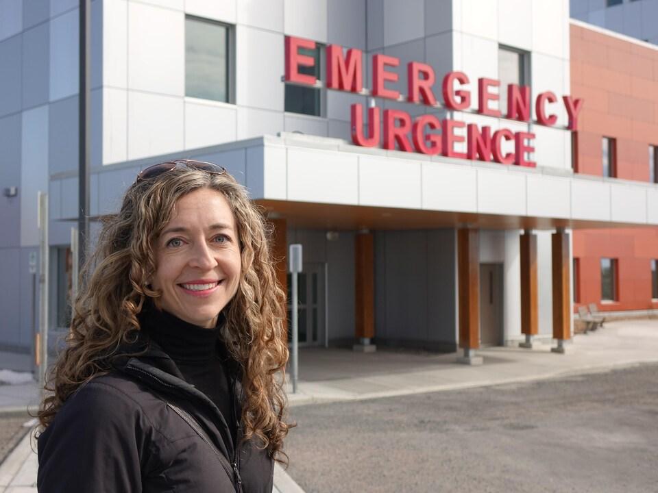 On voit Mme Howard qui sourit à la caméra, devant l'entrée de l'urgence de l'hôpital territorial Stanton.