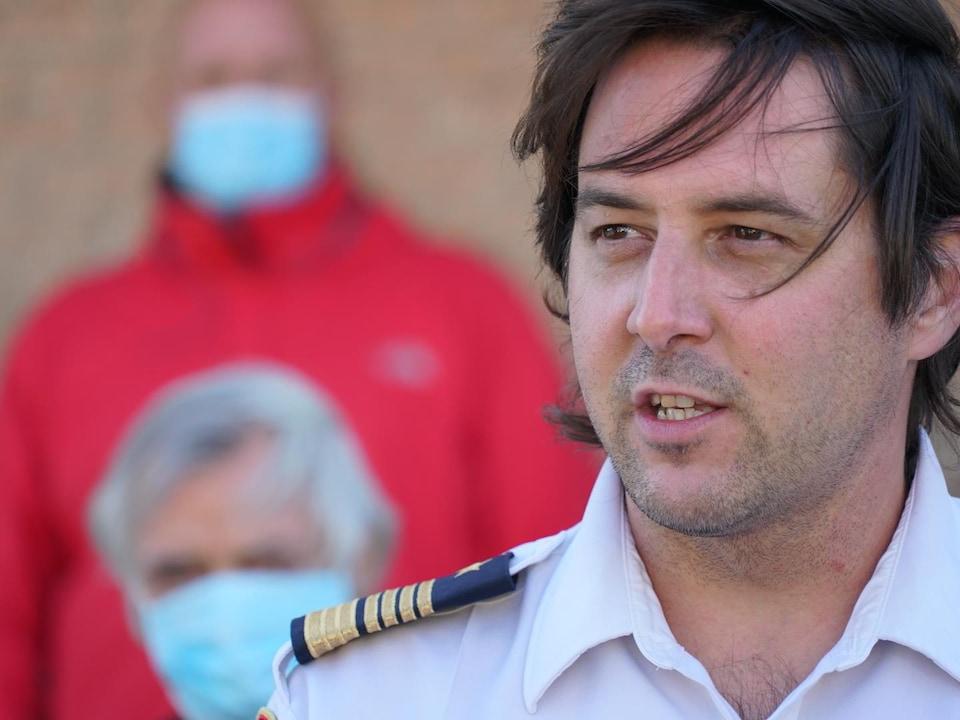 Un homme habillé d'une chemise de pompier parle au micro.