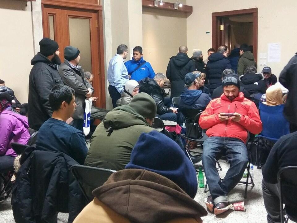 Des gens assis et debout dans la salle d'attente.