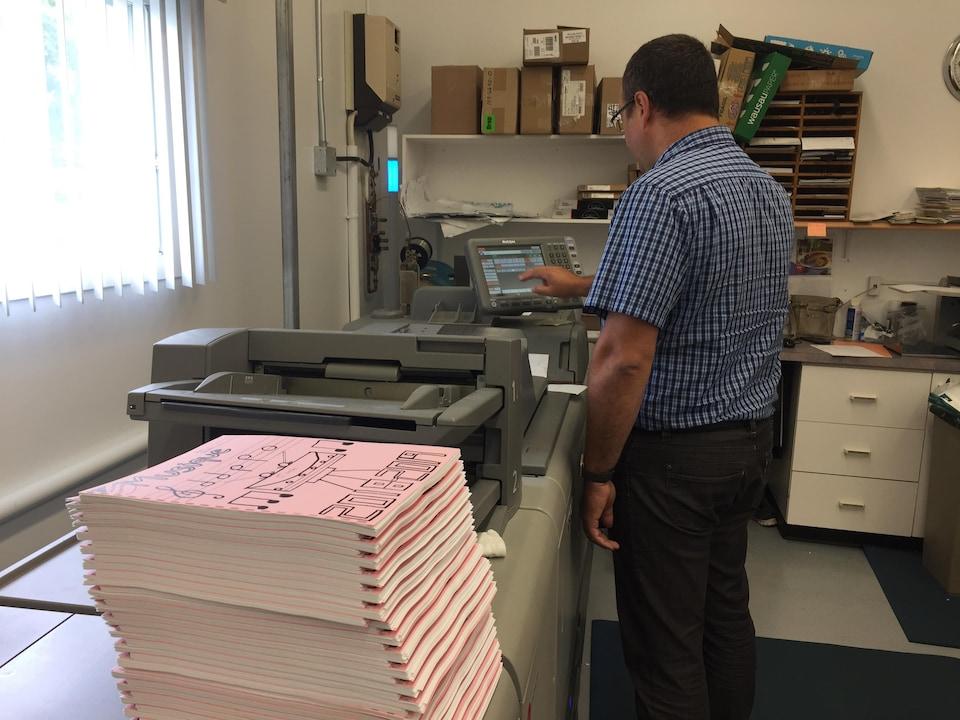 Un homme de dos fait des photocopies dans une imprimerie.