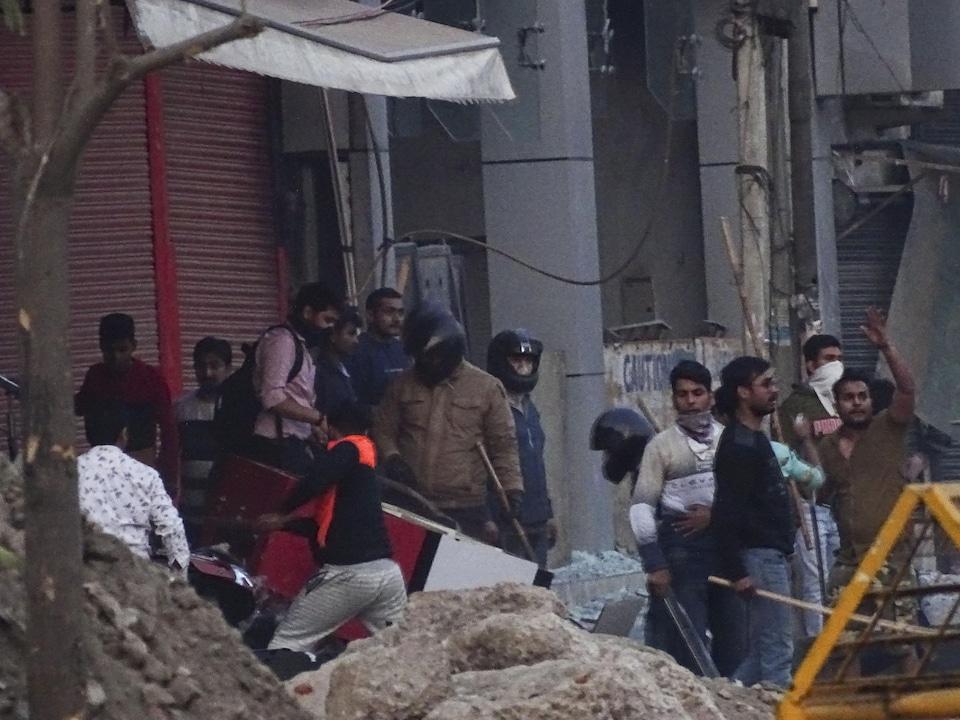 Plusieurs émeutiers portant des bâtons, des casques ou des masques sont visibles près de commerces.