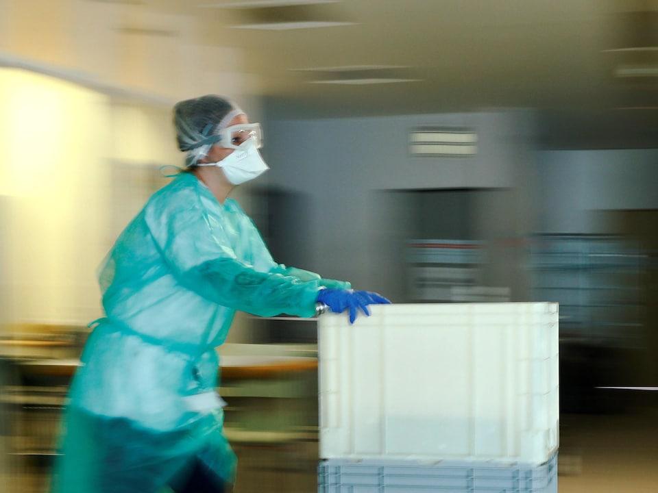 Une infirmière portant un masque et des habits de protection pousse un chariot dans le couloir d'un hôpital.