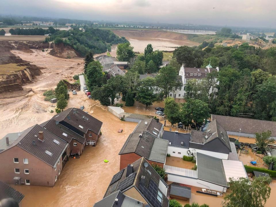 Des maisons entourées de rivières d'eau à proximité du site d'un glissement de terrain.