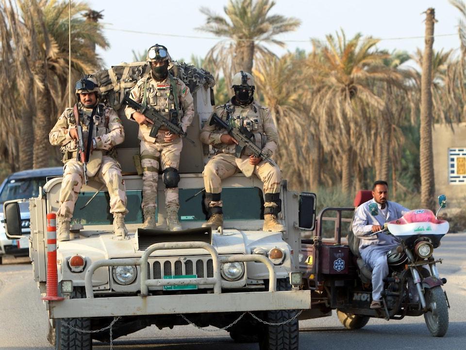 Des soldats irakiens assis sur l'avant d'un véhicule militaire, portant des armes automatiques.