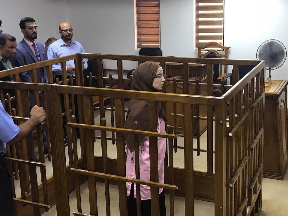 Une femme portant un voile sur la tête est debout à l'intérieur d'une cage en bois dans une salle d'audience d'un tribunal irakien à Bagdad.