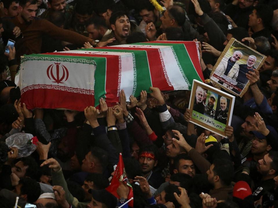 Les manifestants portent le cercueil du général et des photos.