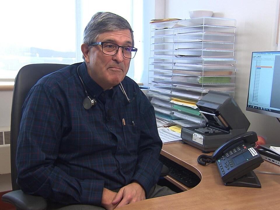 Le Dr Jolivet assis à son bureau.