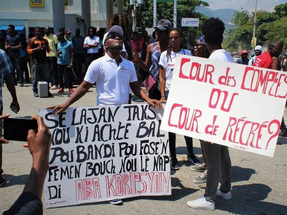 Le manifestant tient une pancarte à l'écart de la foule.