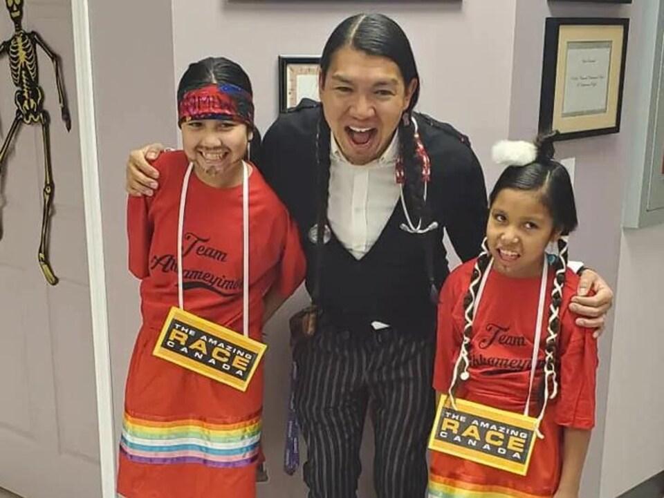 Un homme, tout sourire, est photographié avec deux jeunes filles déguisées en coureurs de la course « The Amazing Race Canada ».