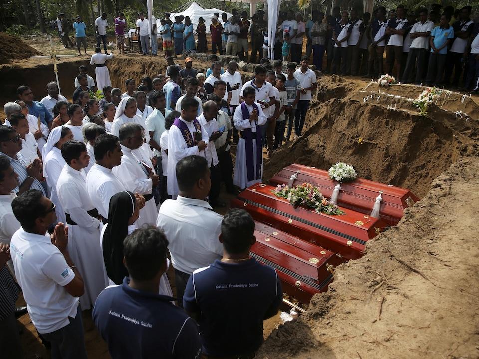 Des gens sont réunis autour de trois cercueils, les mains en signe de prière.