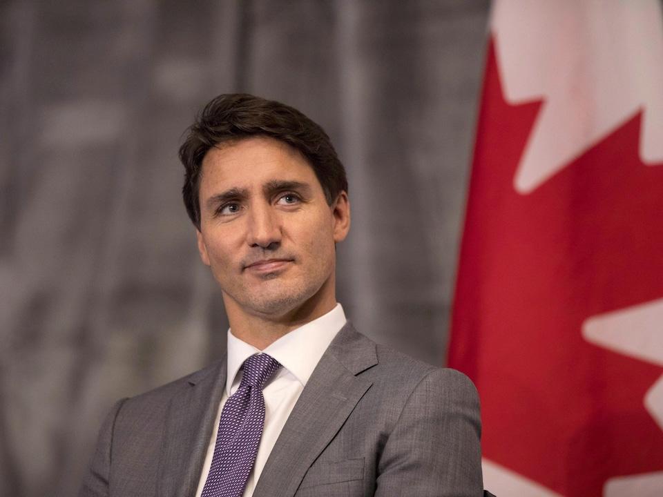 Le premier ministre Justin Trudeau regarde au loin. Derrière lui est accroché un drapeau du Canada.