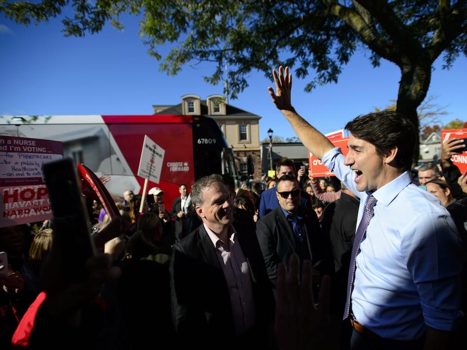 Justin Trudeau salue la foule massée à l'extérieur, près de son autobus de campagne.