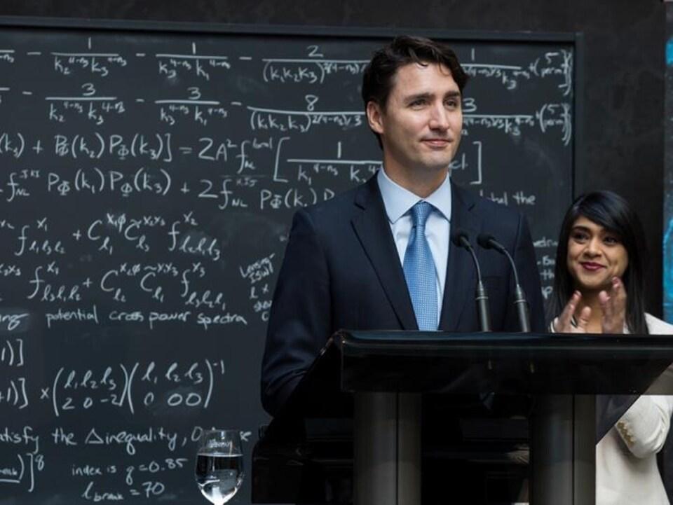 Justin Trudeau devant un tableau de salle de classe.