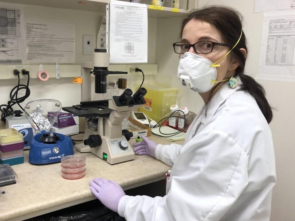 Katia Carmine-Simmen est assise à une table avec un microscope.