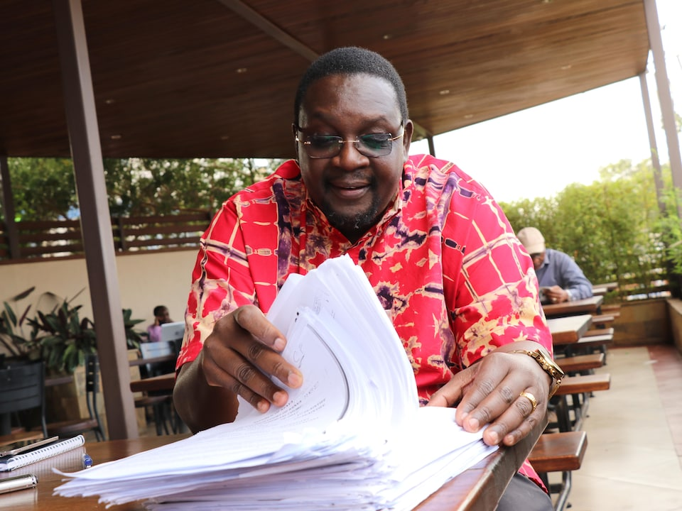 Kennedy Nyagudi regarde des documents de cour