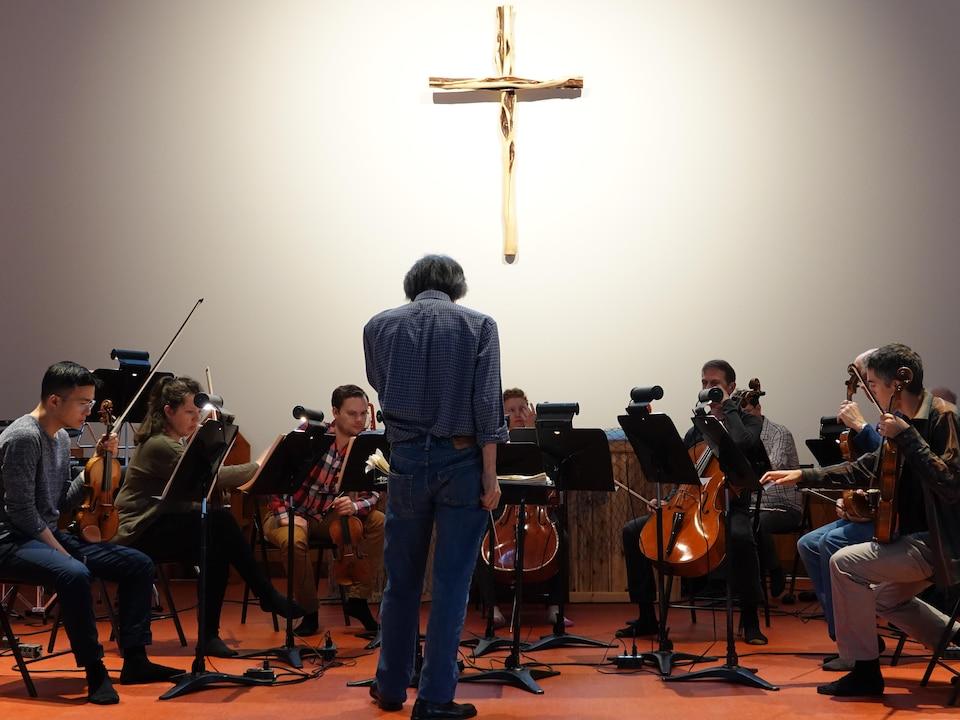 Le maestro debout, devant les musiciens. Sur le mur, une croix.
