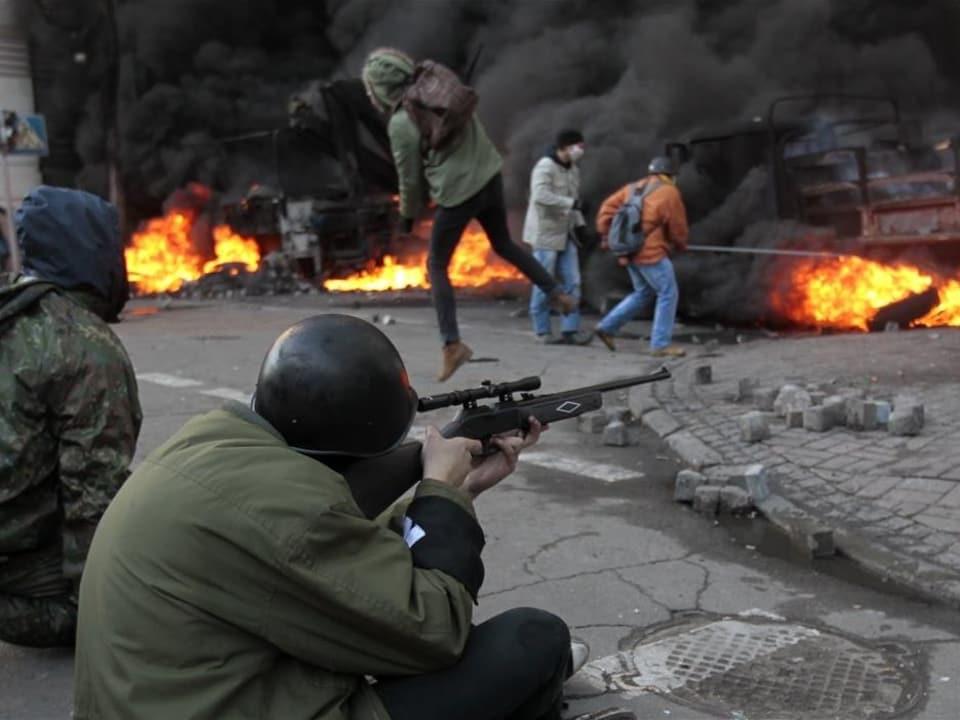 Un protestataire antigouvernemental tire durant des affrontements avec la police, près du parlement ukrainien.